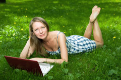 Attractive girl with a laptop in the park stock photography