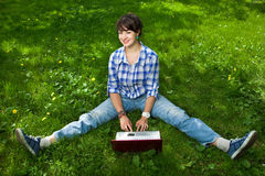 Attractive girl with a laptop in the park royalty free stock image