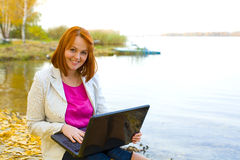 Attractive girl with laptop about a reservoir in the fall Royalty Free Stock Photography