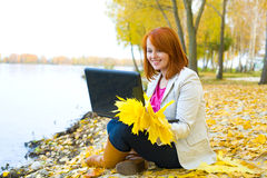 Attractive girl with laptop about a reservoir in the fall Stock Photography