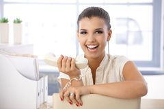 Attractive girl laughing with receiver in hand Royalty Free Stock Image