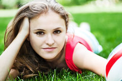Attractive girl lay on grass Stock Photos