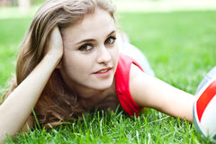 Attractive girl lay on grass Stock Images