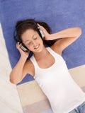 Attractive girl laying on floor enjoying music Royalty Free Stock Image