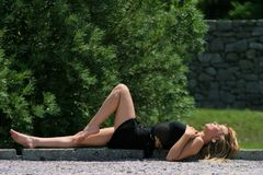 Attractive girl laying outside. Attractive girl in very short black skirt laying outside and enjoying sun with one bare leg lifted in the air Royalty Free Stock Photography