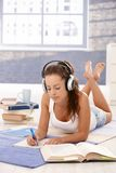 Attractive girl learning at home laying on floor. Using headphones royalty free stock photos
