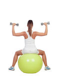 Attractive girl lifting weights sitting on a ball Stock Photo