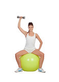 Attractive girl lifting weights sitting on a ball Royalty Free Stock Images