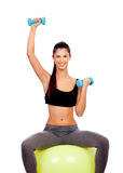 Attractive girl lifting weights sitting on a ball Royalty Free Stock Photos
