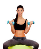 Attractive girl lifting weights sitting on a ball Royalty Free Stock Photo