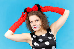 Attractive girl in likeness of cat on blue background posing Royalty Free Stock Photos