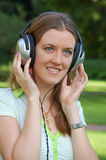 Attractive girl is listening music. On nature Royalty Free Stock Photos