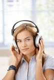 Attractive girl listening music through headphones Royalty Free Stock Photography