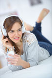 Attractive girl listening to music in bed royalty free stock photo