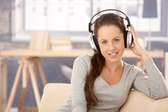 Attractive girl listening to music at home smiling Stock Image