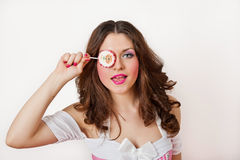 Attractive girl with a lollipop in her hand and pink dress isolated on white. Beautiful long hair brunette playing with a lollipop Royalty Free Stock Images