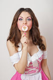 Attractive girl with a lollipop in her hand and pink dress isolated on white. Beautiful long hair brunette playing with a lollipop Royalty Free Stock Photos
