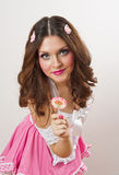 Attractive girl with a lollipop in her hand and pink dress isolated on white. Beautiful long hair brunette playing with a lollipop Stock Photography