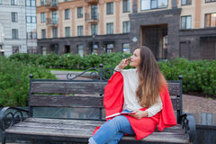 An attractive girl with long brown hair sits on a bench, hiding behind a red rug, gnawing a pen and thinking on an urban backgroun Royalty Free Stock Images