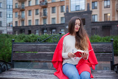 An attractive girl with long brown hair sits on a bench and writes her thoughts on the city background in a red notebook. She wear Stock Photo