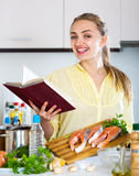 Attractive girl with long hair checking recipes Royalty Free Stock Photography