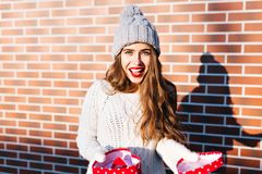 Attractive girl with long hair in knitted hat with open present on wall background outside. She wears warm white sweater. Attractive girl with long hair in royalty free stock image