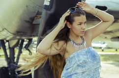 Attractive girl with long hair in sunglasses about aircraft outs Royalty Free Stock Photo