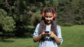 An attractive girl with long hair walks through the park and listens to music in headphones. Slow mothion. An attractive young girl with long hair strolls stock video