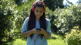 An attractive girl with long hair walks through the park and listens to music in headphones. Slow mothion. HD. An attractive young girl with long hair strolls stock footage