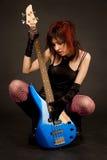Attractive girl looking at bass guitar. Studio shot stock photos