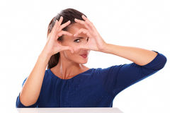 Attractive girl looking through a love sign Royalty Free Stock Photography