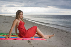 Attractive girl looking to the sea. Attractive girl sitting on a towel, looking to the sea at sunset Royalty Free Stock Photos