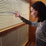 Attractive girl looks out blinds Royalty Free Stock Photo