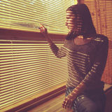 Attractive girl looks out blinds. Attractive young woman looks out blinds. Vintage effect royalty free stock image