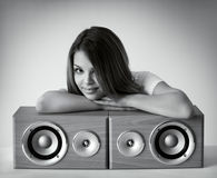 Attractive girl with loudspeakers. On a gray background stock image