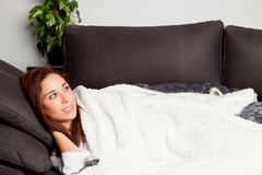 Attractive girl lying on the couch covered with a blanket Stock Image