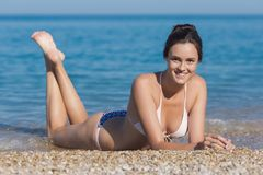 Attractive girl lying on pebble at waters edge. Attractive girl on pebble seashore. Young woman in bikini lying on pebble at waters edge looking at camera Stock Photography