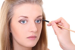 Attractive girl with make-up brush over white Stock Photography