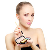 Attractive girl with makeup palette isolated on white Stock Image