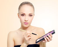 Attractive girl with makeup palette Stock Photography