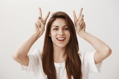 Attractive girl making air quotes. Portrait of charming young female raising hands near head and showing v or peace sign. Smiling broadly, saying ironic things royalty free stock image