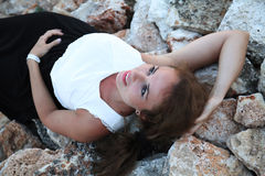 An attractive girl model laying on a bed of rocks at the beach on a sunny day Royalty Free Stock Photography