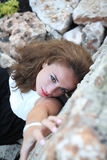 An attractive girl model laying on a bed of rocks at the beach on a sunny day Stock Images