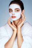 Attractive girl with moisturizing facial mask on blue background royalty free stock photos