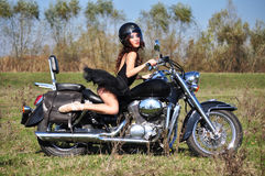 Attractive girl on a motorbike posing outside royalty free stock photo