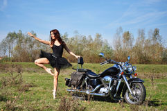 Attractive girl on a motorbike posing outside Stock Photo