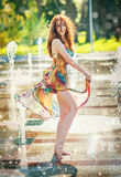 Attractive girl in multicolored short dress playing with water in a summer hottest day. Girl with wet dress enjoying fountains Stock Photos