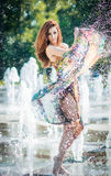 Attractive girl in multicolored short dress playing with water in a summer hottest day. Girl with wet dress enjoying fountains Stock Images