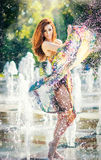 Attractive girl in multicolored short dress playing with water in a summer hottest day. Girl with wet dress enjoying fountains. Young beautiful happy female Stock Photos