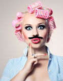 Attractive girl with mustache. And hair curlers stock images